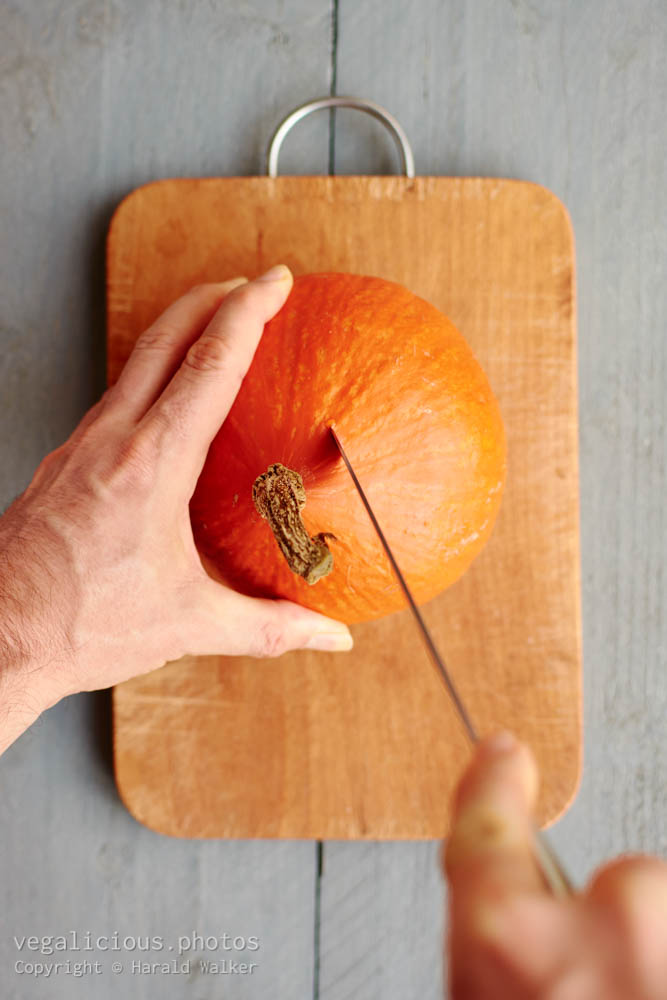 Stock photo of Cutting a red kuri squash