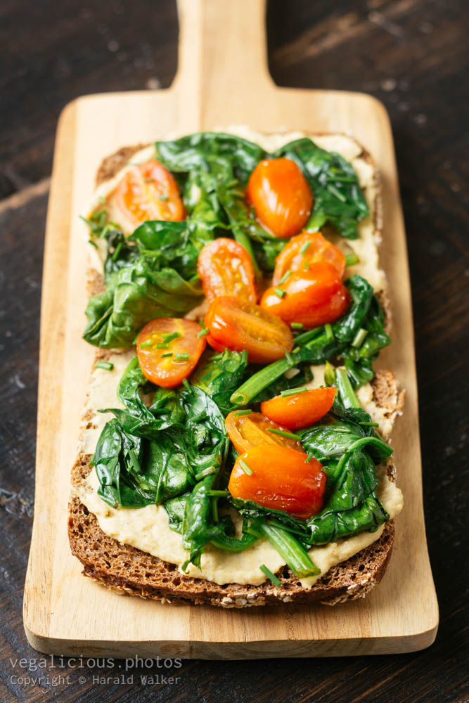 Stock photo of Hummus Toast with Spinach and Cherry Tomatoes